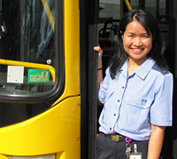 Female bus driver standing in an open bus doorway.