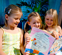 Three little girls reading a picture book