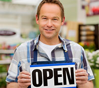 Man holding open sign in front of shop