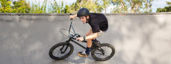 Young male riding BMX bike at skate park