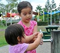 Children at water taps in park