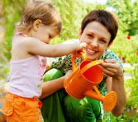 Mother and daughter watering plants with watering can
